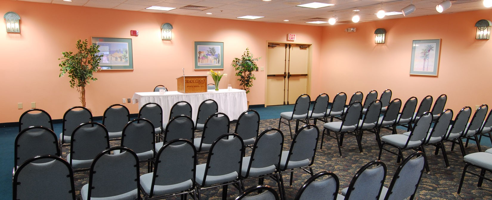 Meeting room with podium and chairs at Beach Colony Resort