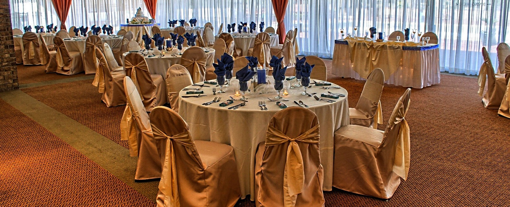 gold and navy wedding place settings and chair wraps at The Caravelle Resort