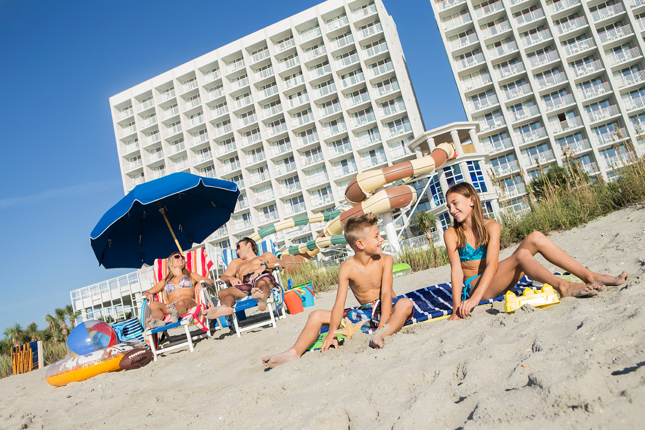 Family on the beach in Myrtle Beach, SC by Crown Reef Beach Resort and Waterpark