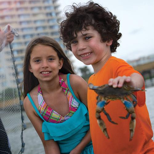 kids holding crab at ocean creek resort beach