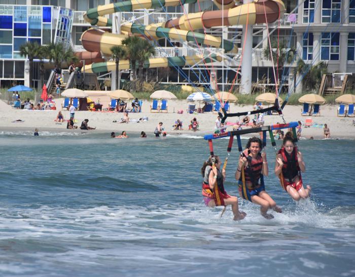 teens parasailing, crown reef resort in background